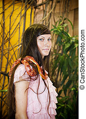 Portrait of beautiful girl with snake in a greenhouse