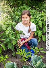 Portrait of beautiful girlspudding soil with trowel between rows of growing vegetables in garden