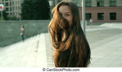 Portrait of beautiful happy girl with long hair that stands on the street