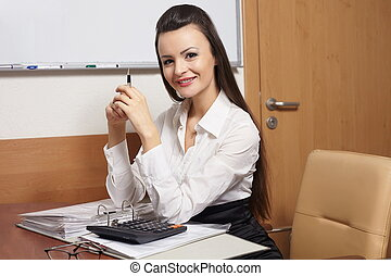 portrait of beautiful happy smiling business woman sitting at the desk in the office