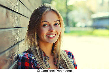 Portrait of beautiful happy smiling young woman in a city