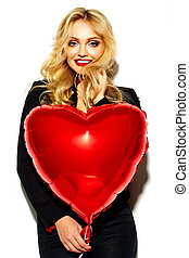 portrait of beautiful happy sweet smiling blonde woman girl holding in her hands red heart balloon in casual black hipster clothes