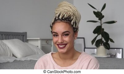 Portrait of beautiful happy young hipster woman with dreadlocks in room