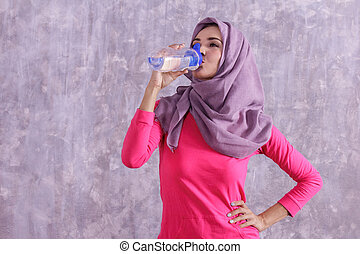 beautiful hijab sporty woman drinking mineral water after workou