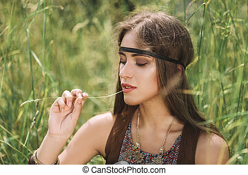 portrait of beautiful hippie girl sitting on grass