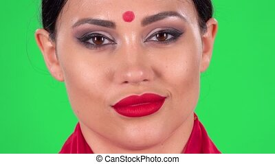 Portrait of beautiful Indian woman is looking at the camera flirts, raises eyebrows, winks and blows a kiss. Green screen. Close up. Macro shooting.
