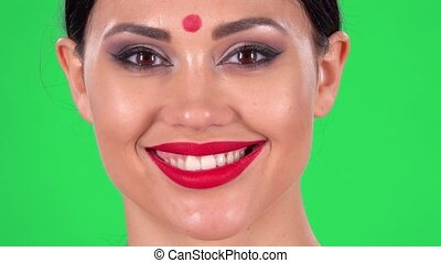 Portrait of beautiful Indian woman is looking seriously at the camera and then smiling. Green screen. Close up. Macro shooting.