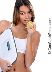 portrait of beautiful Latina eating apple with scales