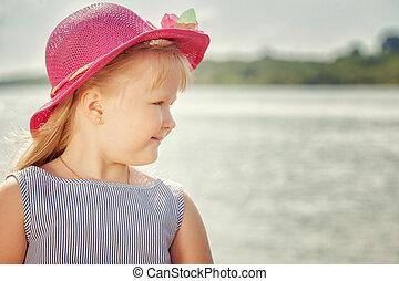 Portrait of beautiful little blond girl in hat