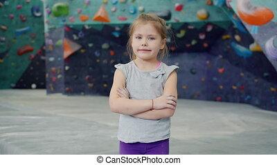 Portrait of beautiful little girl in indoor climbing ...