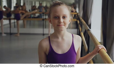 Portrait of beautiful little girl starting ballet-dancer looking at camera and smiling standing in ballet class in spacious light dancehall. Art and childhood concept.