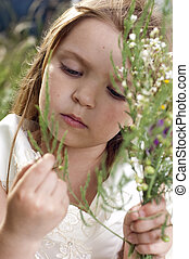 Portrait of beautiful little girl with the field flowers