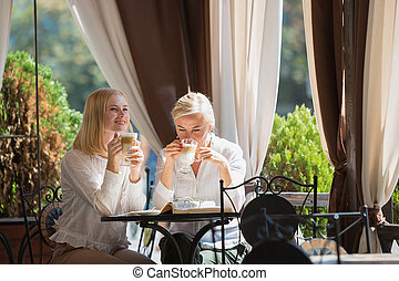 Portrait of beautiful mature mother and her daughter holding cup sitting at home