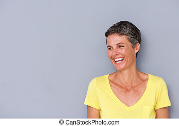 beautiful middle age woman laughing by gray wall
