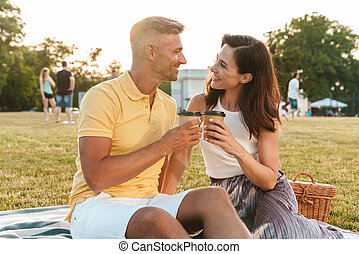 Portrait of beautiful middle-aged couple drinking coffee takeaway from paper cup while sitting on grass in park