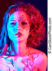 portrait of beautiful model with skew bodyart and hairdo in mixed red/blue light
