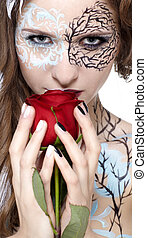 portrait of beautiful model with skew bodyart and hairdo posing with red rose