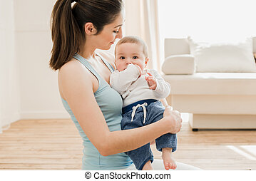 Portrait of beautiful mother holding child to her chest at home