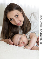 Portrait of beautiful mother with her 7 months old baby sleeping in the bed