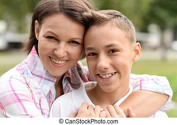 Portrait of beautiful mother with son in park