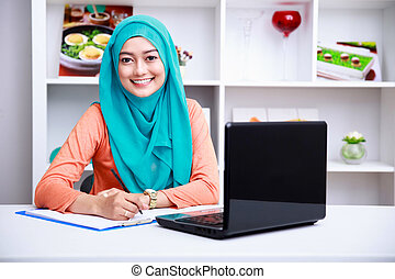 beautiful muslim woman writing an information from laptop -...