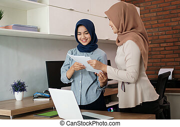 portrait of beautiful muslim women smile while explaining project on paper to her partner