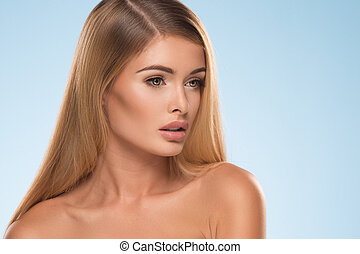 Portrait of beautiful natural blonde woman on blue background