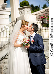 beautiful newlyweds kissing at sunny day on street
