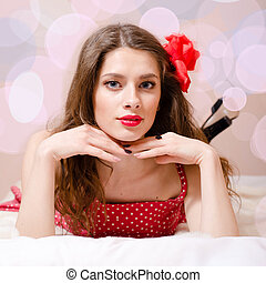 portrait of beautiful pinup girl with red lipstick having fun relaxing in bed & looking at camera on light copy space background