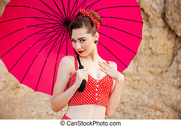 Portrait of beautiful pinup girl with umbrella at the beach