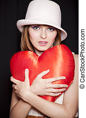 Portrait of beautiful redhead girl with toy heart.