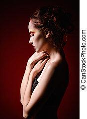 Portrait of a beautiful sad redhead girl. Profile view