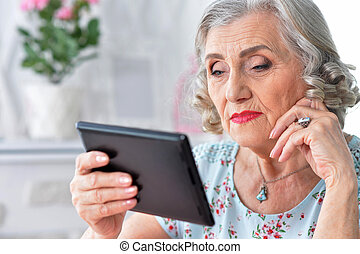 Portrait of beautiful senior woman using modern tablet