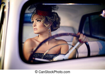 Portrait of beautiful sexy fashion stylish blond girl model with bright makeup in retro style sitting in old car