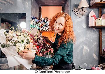 portrait of beautiful shop assistant taking two flower bouquets in flower shop