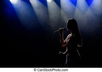 Portrait of beautiful singing woman on dark background