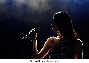 Portrait of beautiful singing woman on dark background