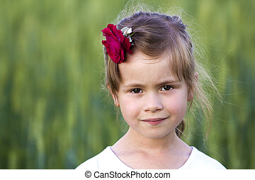 Portrait of beautiful small preschool blond girl with nice gray eyes and red rose in hair smiling dreamily in camera on blurred bright green background. Happy careless childhood concept.