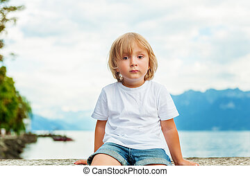 Portrait of beautiful smiling cute little boy. 3-4 years old little child playing outside by the lake Geneva, in summer or spring. Boy sitting alone by the lakeside at sunset, wearing white t-shirt