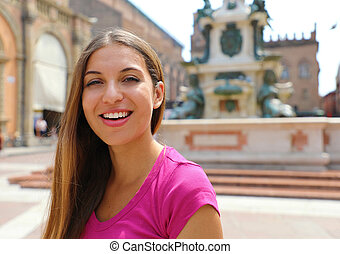 Portrait of beautiful smiling girl in Bologna city, Italy.