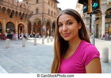 Portrait of beautiful smiling girl posing outdoor with city on background. Copy space.