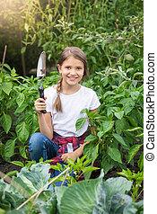 Portrait of beautiful smiling girl posing with trowel in garden