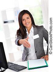 Portrait of beautiful smiling hostess giving handshake
