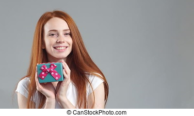 Portrait of beautiful smiling redhead girl hold gift box in hands.