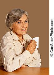 Portrait of beautiful smiling senior woman drinking tea
