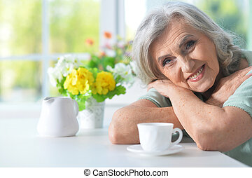 Portrait of beautiful smiling senior woman with cup of tea at kitchen