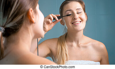 Portrait of beautiful smiling woman applying mascara at bathroom