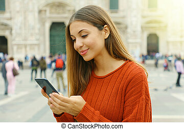 Portrait of beautiful smiling woman typing on smart phone outdoor.