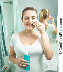 beautiful smiling woman using moisturizing lotion at bathroom