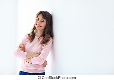 Portrait of beautiful smiling woman with crossed arms on white background
